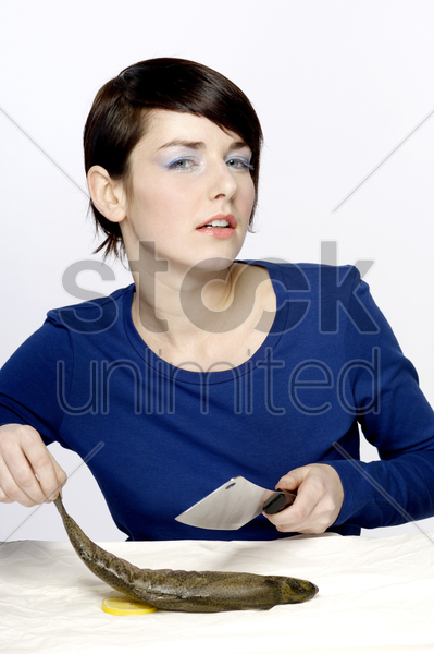 woman trying to cut fish with knife stock photo