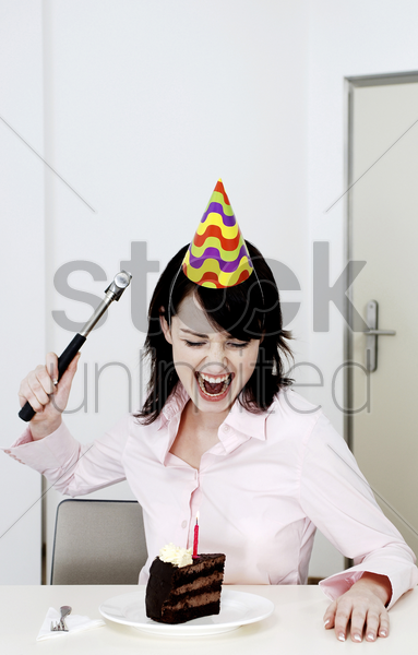 woman trying to hammer her birthday cake stock photo