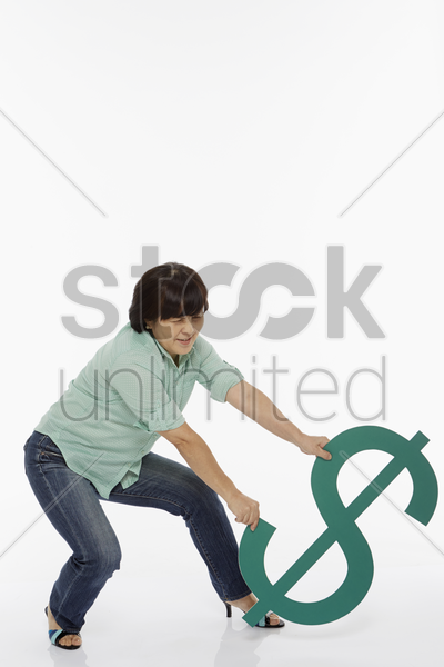 woman trying to lift up the dollar sign stock photo