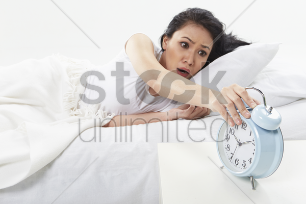 woman turning off alarm clock stock photo