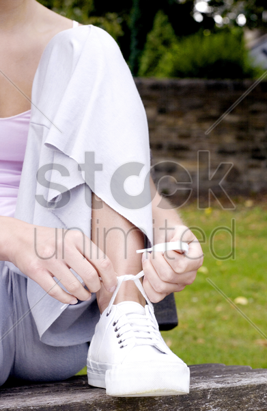 woman tying her shoe lace stock photo