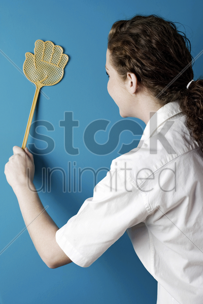 woman using a fly swatter stock photo