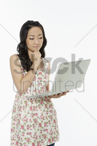 woman using a laptop while standing, contemplating stock photo