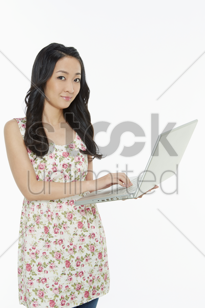 woman using a laptop while standing stock photo
