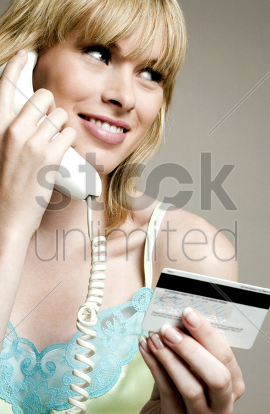 woman using credit card over the telephone stock photo