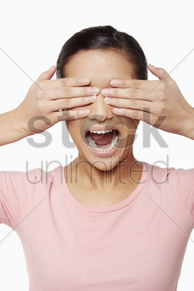 woman using her hands to cover her eyes stock photo