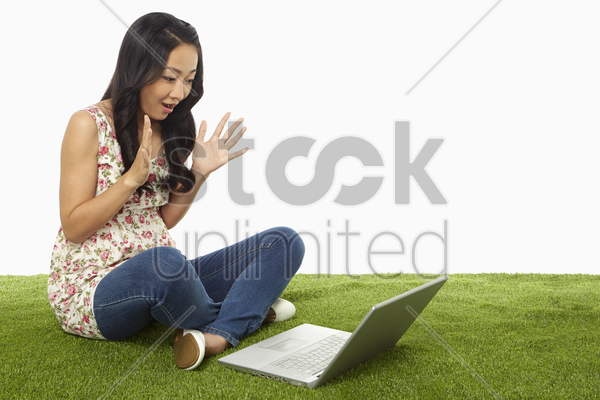 woman using laptop and looking surprised stock photo