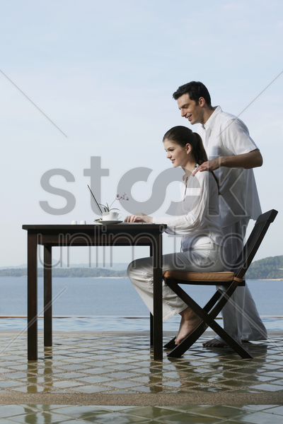 woman using laptop by the pool side, man watching from behind stock photo