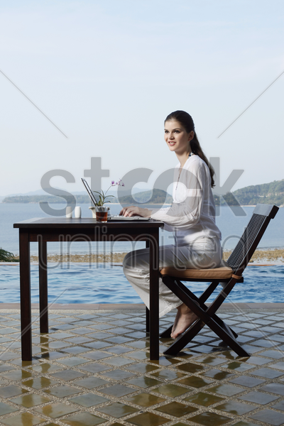 woman using laptop by the pool side stock photo