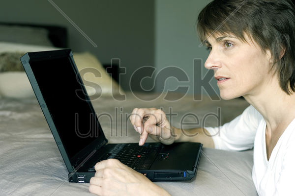 woman using laptop in the bedroom stock photo