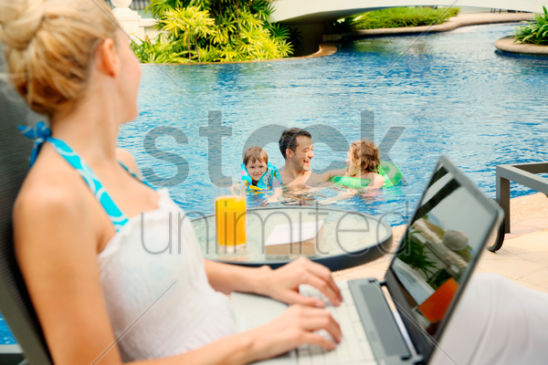 woman using laptop looking at her family in the pool stock photo