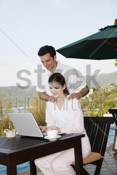 woman using laptop, man watching from behind stock photo