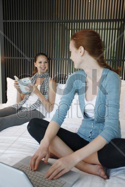 woman using laptop talking to another woman who is reading book stock photo