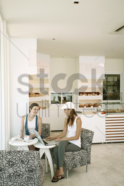 woman using laptop while another woman is writing in organizer at bakery stock photo
