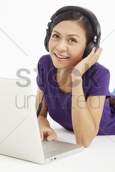 woman using laptop while listening to music stock photo