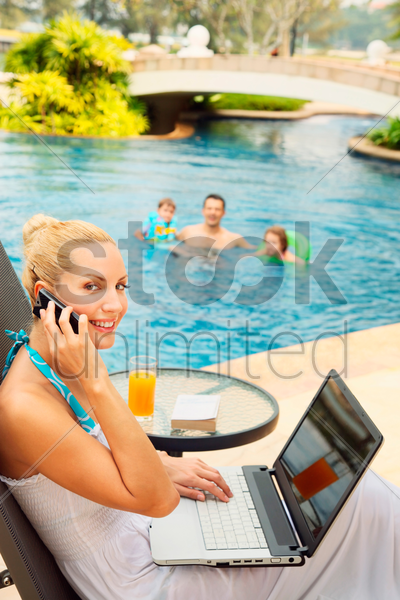 woman using laptop while talking on the phone stock photo