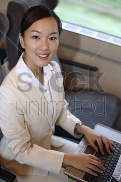 woman using laptop while traveling on the train stock photo