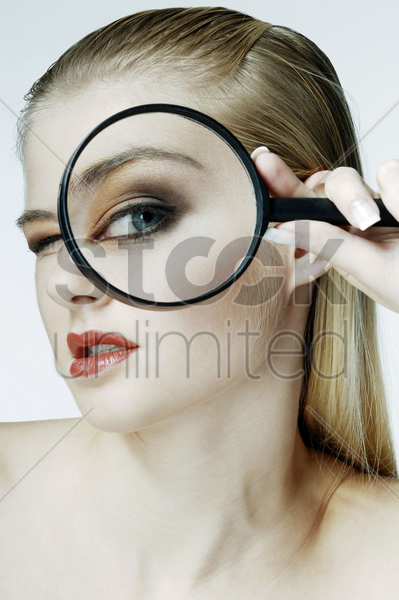 woman using magnifying glass stock photo