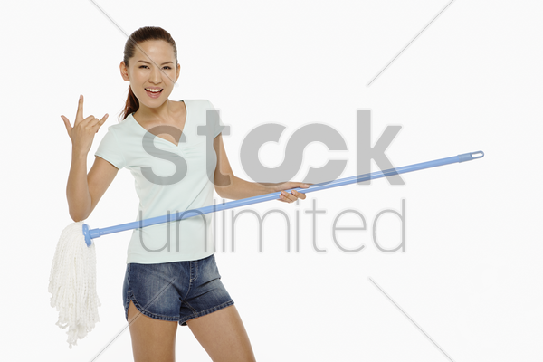 woman using mop as a guitar stock photo