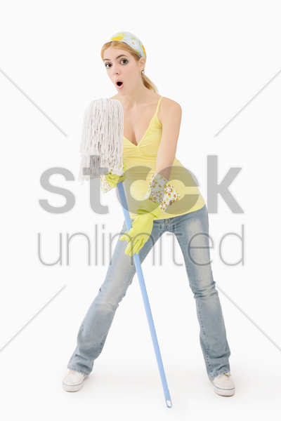 woman using mop as microphone stock photo