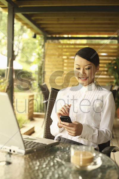 woman using pda phone, smiling stock photo