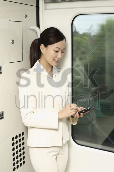 woman using pda phone while traveling in train stock photo