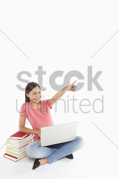 woman using the laptop, pointing at one direction stock photo
