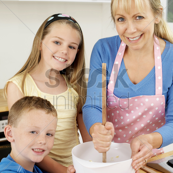 woman using wooden ladle, boy and girl smiling at the camera stock photo