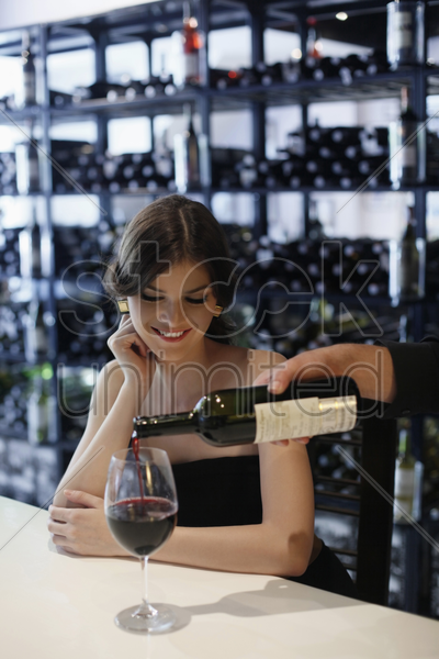 woman waiting for her wine to be poured stock photo