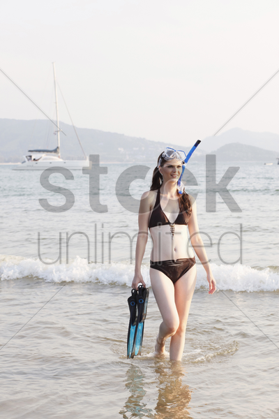 woman walking through water, holding flippers stock photo