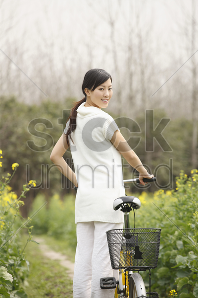 woman walking with bicycle stock photo