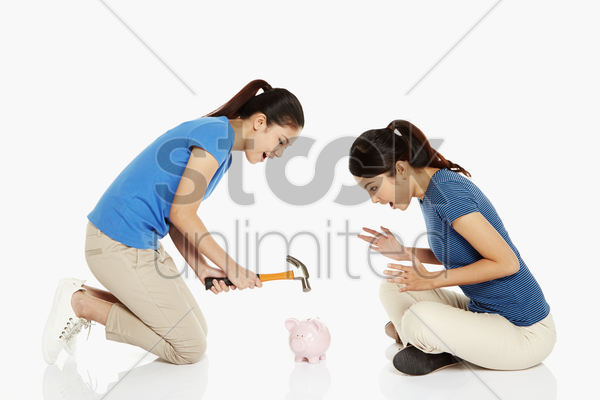 woman wanting to hit the piggy bank with a hammer stock photo