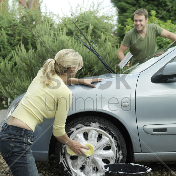 woman washing car wheel, man washing windshield with squeegee stock photo