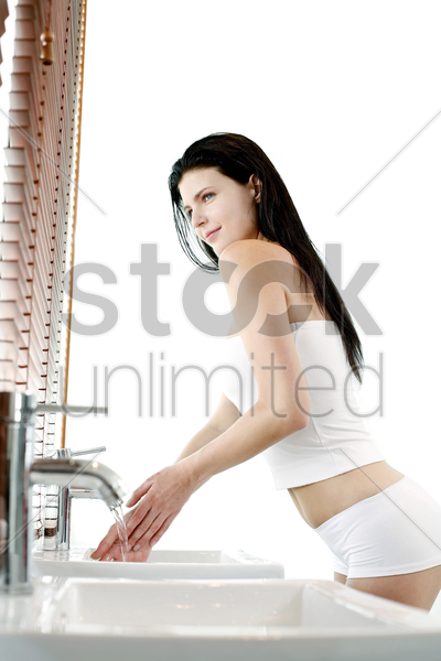 woman washing hands in the bathroom stock photo