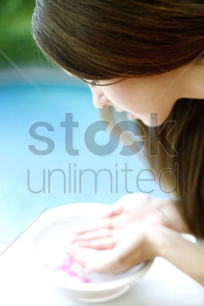 woman washing her face with flower water stock photo