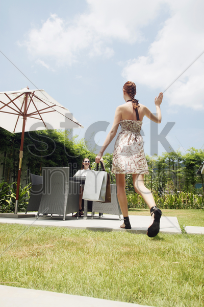 woman waving at her friend who has arrived stock photo