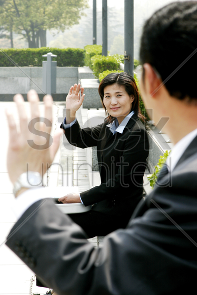woman waving to her manager stock photo