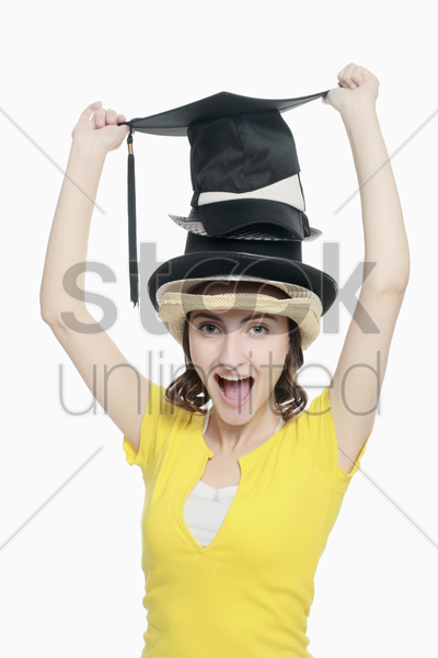 woman wearing a stack of different hats stock photo