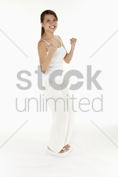 woman weighing herself on the scale stock photo