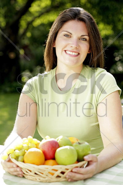 woman with a basket of fruits stock photo