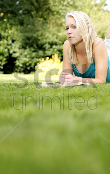 woman with a book on the grass looking at the camera stock photo