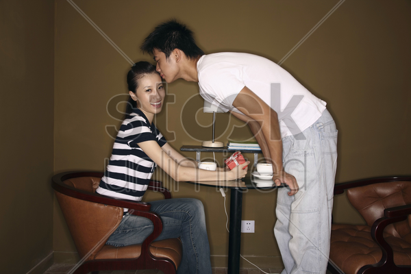 woman with a box of gift receiving a kiss from man stock photo