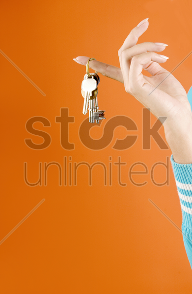 woman with a bunch of keys hanging on her finger stock photo