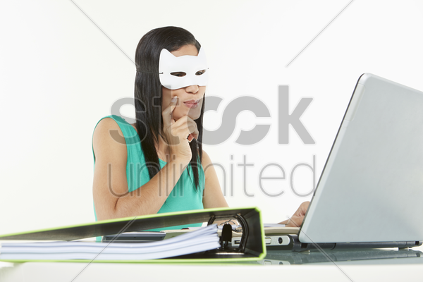 woman with a cat mask using laptop stock photo