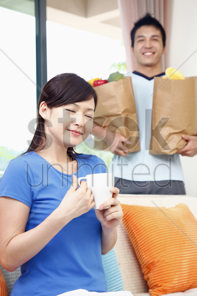 woman with a cup of coffee, man carrying groceries in the background stock photo