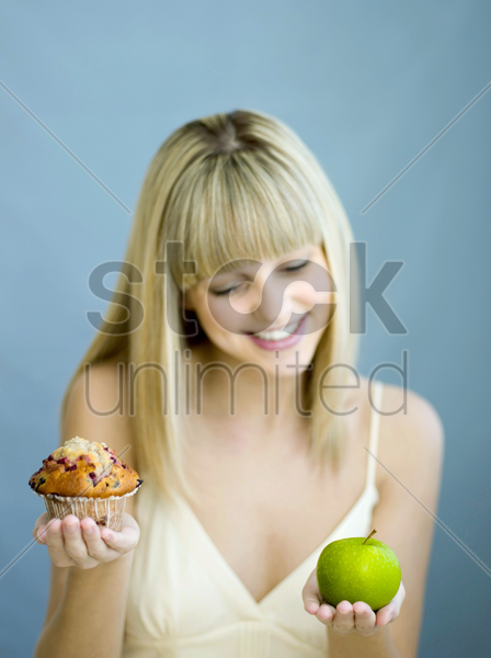woman with a cupcake and green apple stock photo