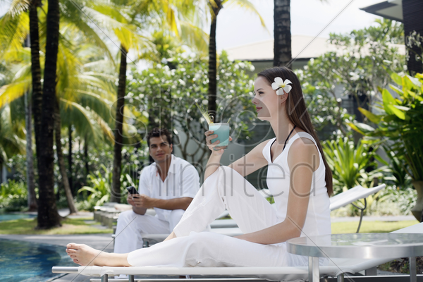 woman with a glass of cocktail sitting on lounge chair, man text messaging in the background stock photo