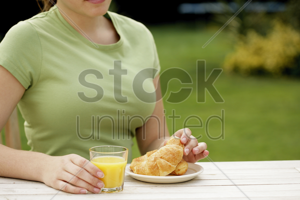 woman with a glass of orange juice and a plate of croissants stock photo