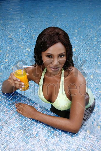 woman with a glass of orange juice leaning on pool edge stock photo