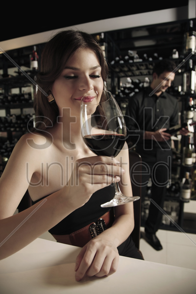 woman with a glass of red wine, man selecting wine bottle in the background stock photo